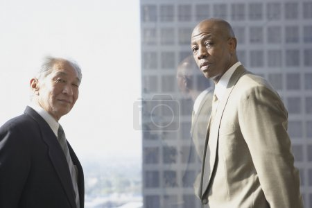 Two businessmen in front of window