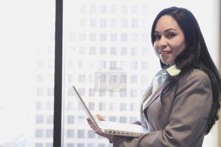 Hispanic businesswoman with laptop next to window