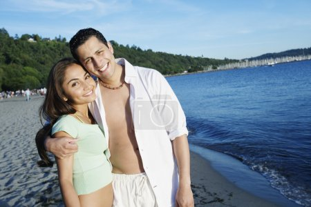 Happy couple standing together on beach