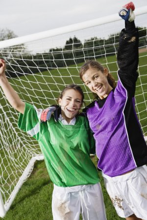 Two friends cheering in front of soccer net