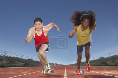 Two male track participants race