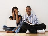 Mladý pár pomocí mobilních telefonů a notebooků
