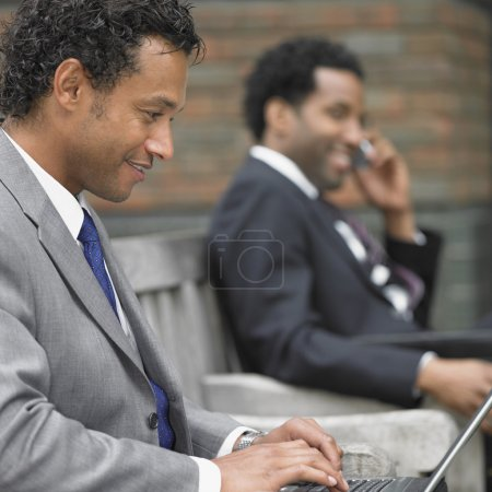 Two businessmen working on outdoor bench