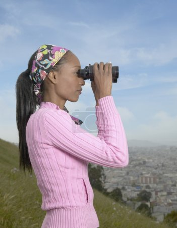 African woman using binoculars over city