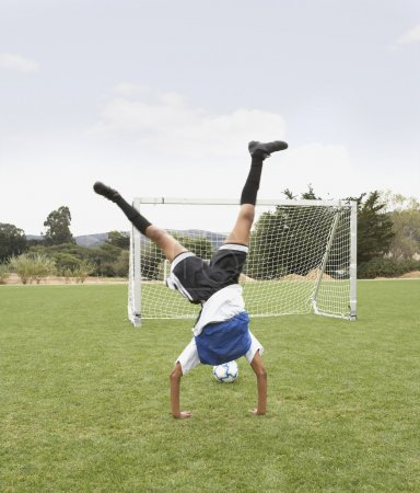 Young girl doing a cartwheel on soccer pitch