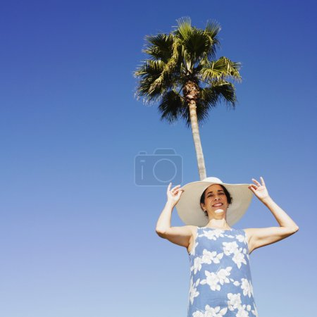Hispanic woman wearing sunhat under palm tree