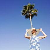 Hispanic woman wearing sunhat under palm tree