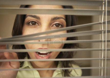 Portrait of businesswoman peering through blinds