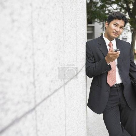 Businessman leaning against wall with cell phone