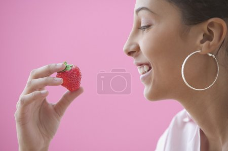 Profile of teen girl holding a strawberry