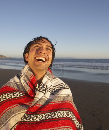 Portrait of man wrapped in blanket laughing at beach