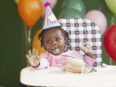 African baby in high chair wearing party hat and eating cake