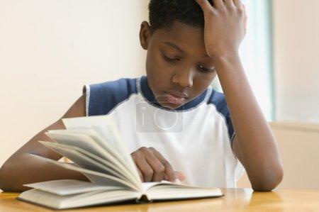 African American boy reading book