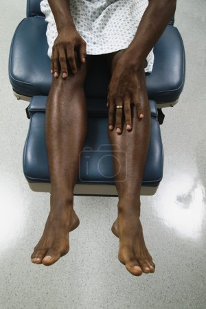 Low section of male patient in gown
