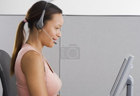 Side view of woman in office with headpiece in front of computer