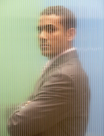 Businessman obscured by glass wall