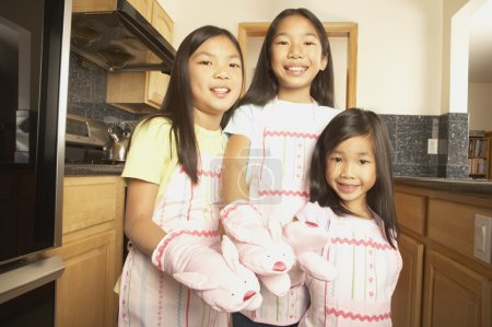 Three young Asian sisters wearing aprons and bunny oven mitts in the kitchen