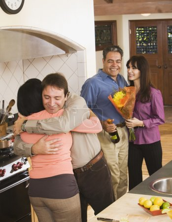 Middle-aged friends hugging in kitchen