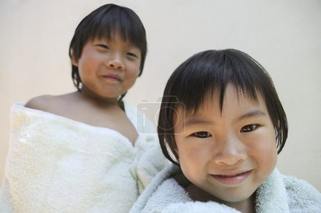 Sister and brother wrapped up in towels