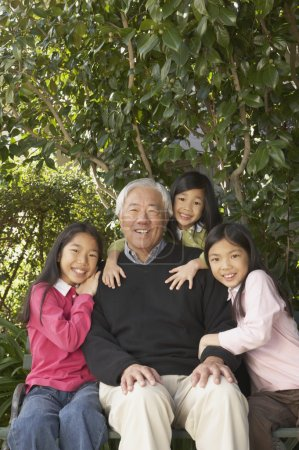 Asian grandfather with granddaughters outdoors