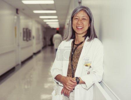 Mature female doctor in hospital hallway