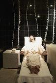 Muž v rouchu, seděl v křesle ve wellness místnosti