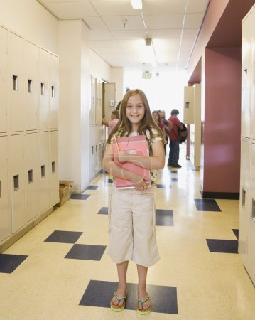 Girl holding notebook in school hallway