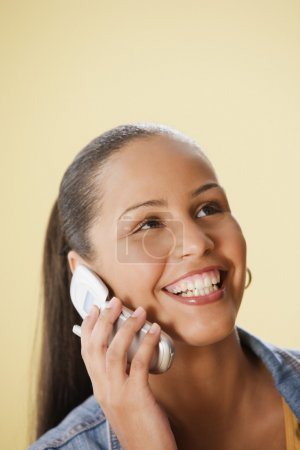 Studio shot of a female Dominican teenager talking on cell phone