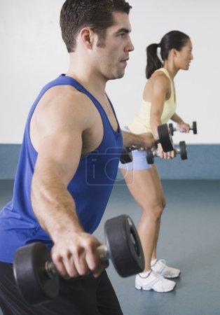 Man and woman lifting weights at gym
