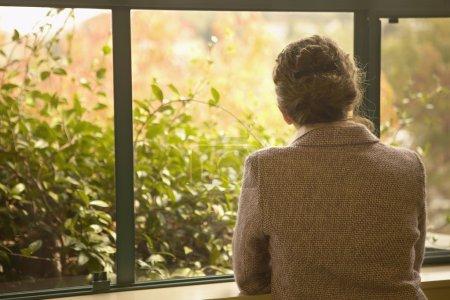vue arrière de femme regardant dehors la fenêtre