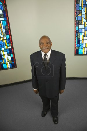 High angle view of senior African man next to stained glass windows