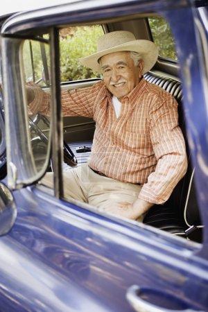 Portrait of elderly man sitting in old pickup truck