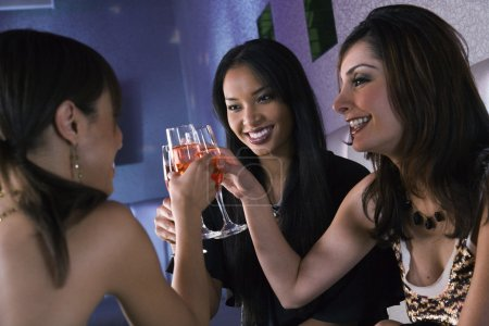 Multi-ethnic women toasting with cocktails