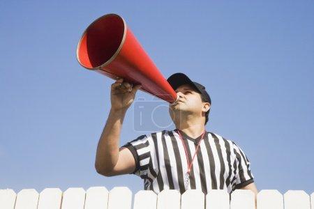 Hispanic referee yelling over fence
