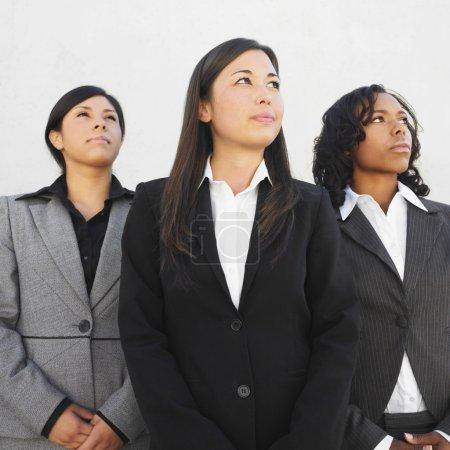 Multi-ethnic businesswomen looking up