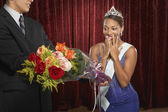 Beauty queen gasping and receiving flowers
