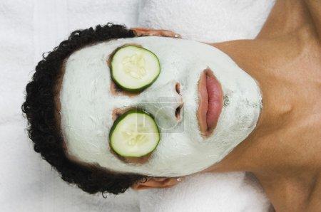 Mixed Race man receiving spa facial treatment