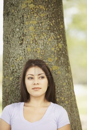 Hispanic woman leaning against tree