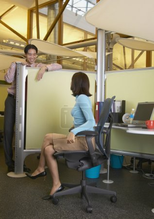Business talking over cubicle wall