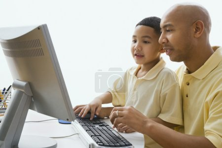 Indian father and son looking at computer