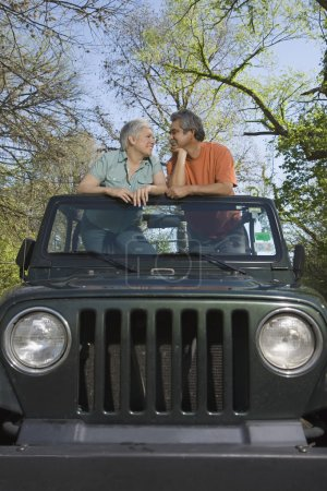 Senior Hispanic couple standing in jeep