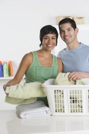 Hispanic couple folding laundry