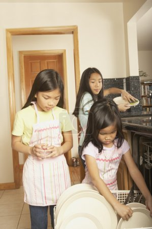Three young Asian sisters doing the dishes
