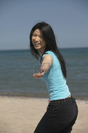 Asian woman laughing with outstretched hand at beach