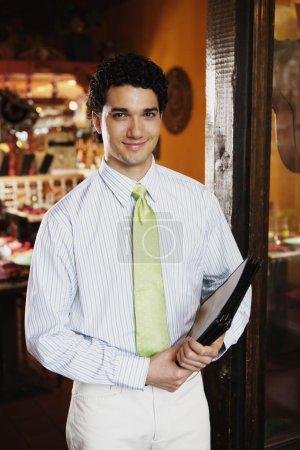 Portrait of waiter holding menus in restaurant