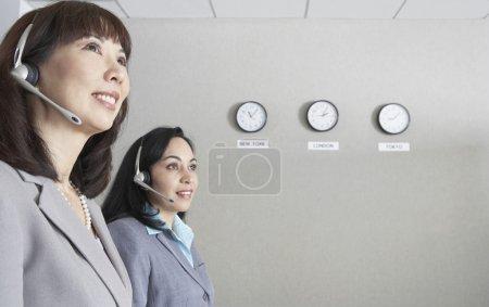 Two businesswomen next to world time zone clocks