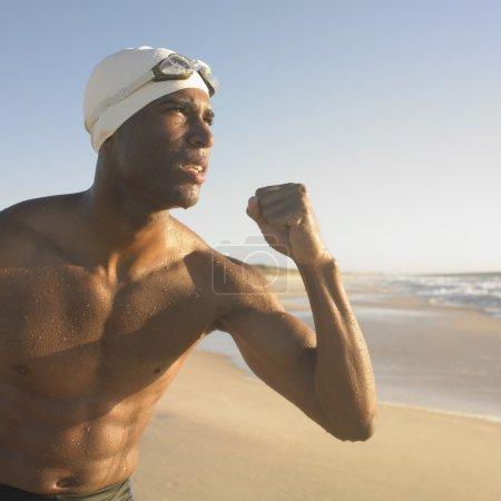 Man in swimming cap flexing muscles