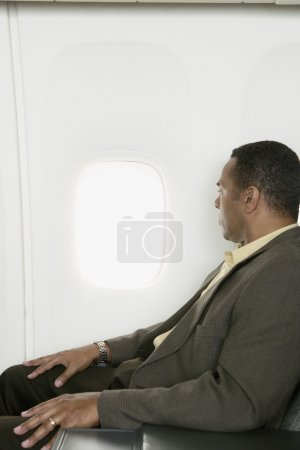 Businessman looking out window on airplane