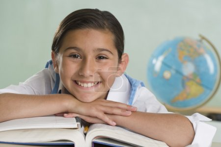Hispanic girl leaning on textbooks and smiling