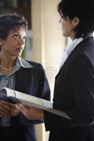 Two multi-ethnic businesswomen talking